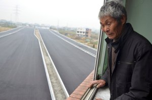 An old man looks down from his house which stands alone in the middle of a newly built road in Wenling, Zhejiang province